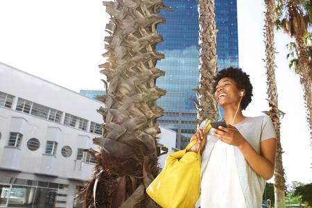 라이프 스타일: 행복 한 젊은 여자와 그녀의 휴대 전화에 음악을 듣고 도시 거리에 핸드백의 초상화