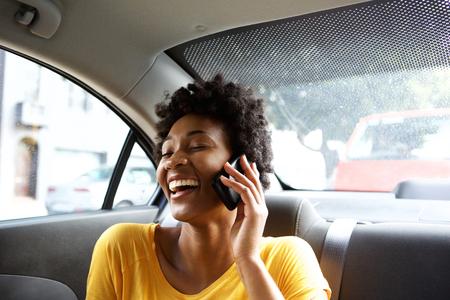 asiento: Retrato de detalle de la mujer de risa joven africano sentado en un asiento trasero de un coche y hablando por tel�fono m�vil