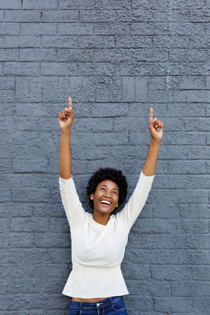 Portrait of a smiling african woman celebrating her success against a gray wall