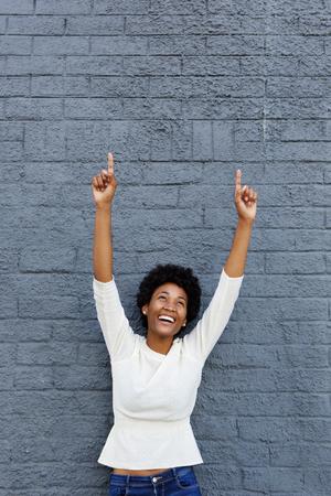 Portret van een glimlachende Afrikaanse vrouw viert haar succes tegen een grijze muur