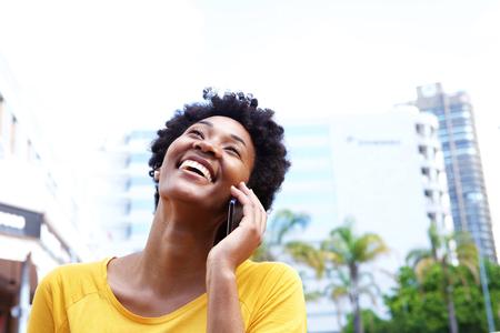 Close-up portret van een vrolijke jonge vrouw te praten over de mobiele telefoon buiten in de stad