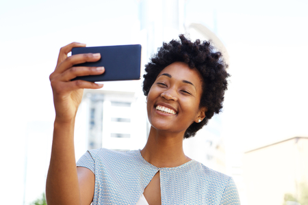 cell phones: Happy young african american woman taking a selfie with her mobile phone Stock Photo