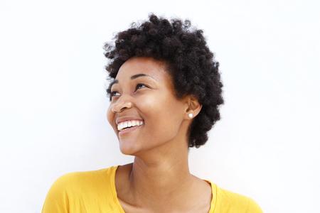 Close-up portret van gelukkige jonge Afrikaanse vrouw op zoek weg tegen een witte achtergrond