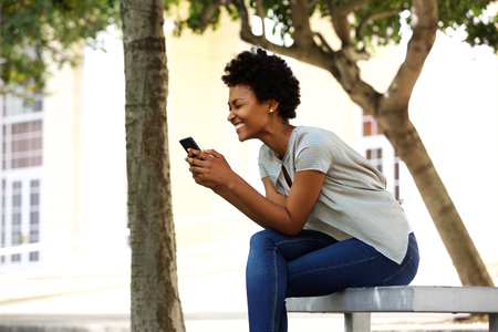 people: Side portrait of cheerful young woman sitting outside on a bench reading a text message on her mobile phone