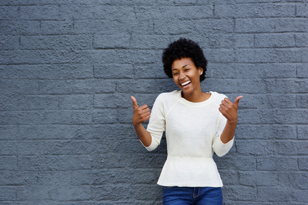 Portrait of smiling young african american woman gesturing thumbs up sign with both her hands against gray wall