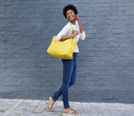 mujeres africanas: Retrato de cuerpo entero de una mujer joven afroamericano caminando con una bolsa y hablando por teléfono móvil