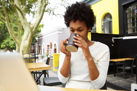 person sitting: Retrato de joven mujer afroamericana sentado en el caf� al aire libre de beber una taza de t� Foto de archivo