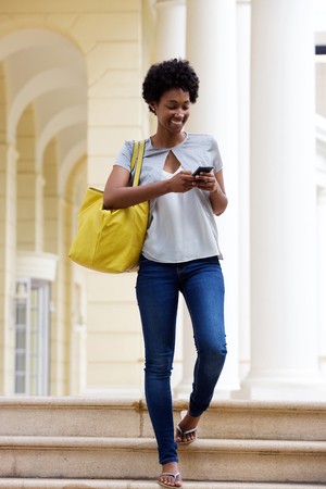 Full body portrait of young african woman coming down the steps of a building and sending text message from her mobile phone