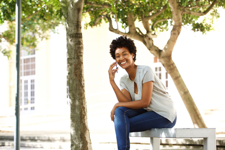 woman street: Portrait of happy african woman sitting on a bench outdoors in city and talking on mobile phone