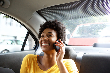 sitting: Closeup portrait of smiling young black woman sitting in a car talking on mobile phone
