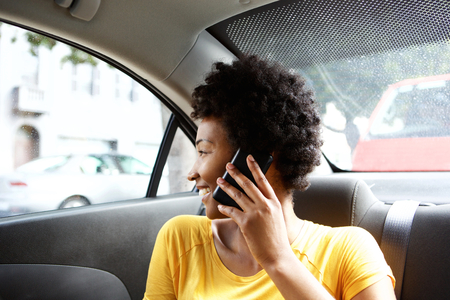 back seat: Close up portrait of young african woman sitting in back seat of a car with mobile phone Stock Photo