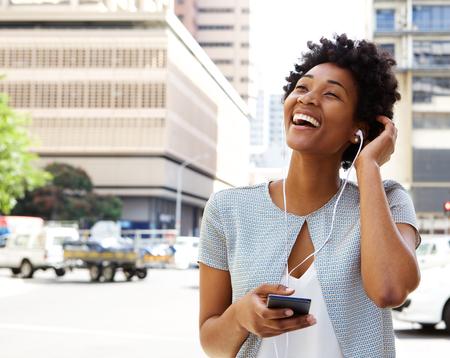 Portret van lachende jonge Afro-Amerikaanse vrouw, het luisteren naar muziek op de koptelefoon buiten op straat in de stad