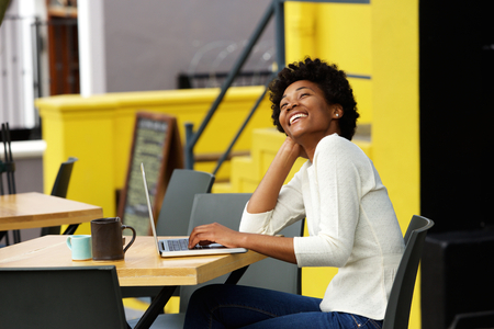 african student: Portrait of an african american woman laughing with laptop at cafe Stock Photo