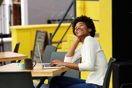 caras felices: Retrato de una mujer de raza negra de risa con la computadora portátil en el café