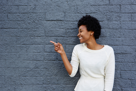 pointing: Portrait of happy young african woman pointing at copy space on gray wall