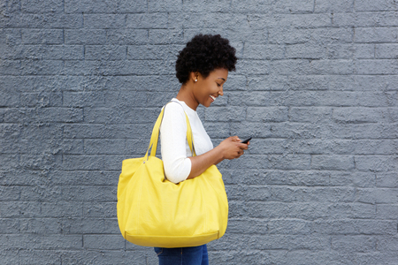 Side portrait of a happy young woman with a bag reading text message on her mobile phone Stockfoto