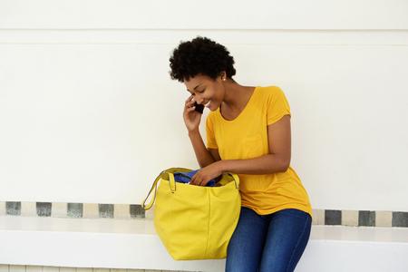 Retrato de una mujer africana joven que se coloca al aire libre que hace una llamada de teléfono y mira dentro de su bolso de mano