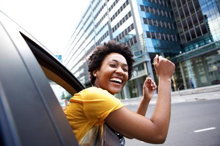 excitación: Alegre retrato de joven mujer africana mirando por la ventana del coche con los brazos levantados