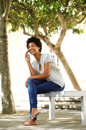 Full body portrait of smiling young african woman sitting on a bench outdoors talking on mobile phone photo