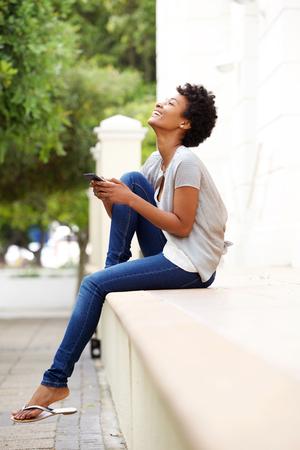modelos negras: Retrato de la cara de una mujer joven feliz que se sienta por una calle con un tel�fono m�vil Foto de archivo