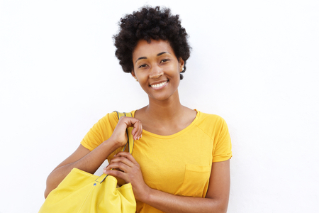 Closeup portrait of beautiful young woman carrying a bag against white background photo