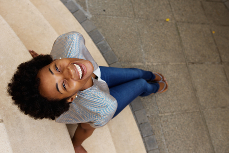 Overhead portrait of smiling young african woman sitting on steps and looking up