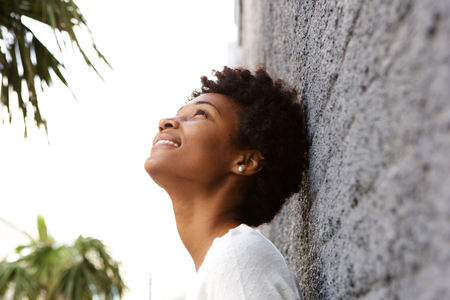 Zij portret van jonge Afrikaanse vrouw leunend tegen een muur buiten en het opzoeken van