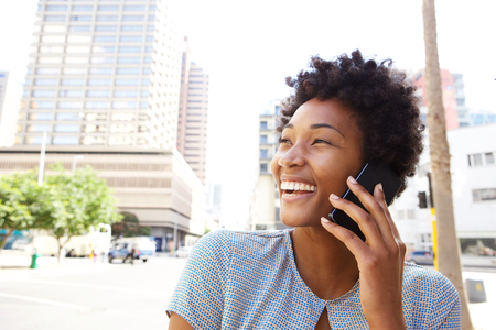 Closeup portrait of a cheerful young woman making a phone call outdoors in the city photo