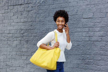 black lady: Portrait of a beautiful young woman with bag walking and talking on cellphone