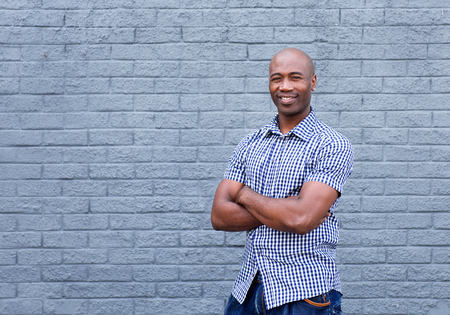 Portrait of smiling african american man standing with arms crossed against a gray wall Stockfoto