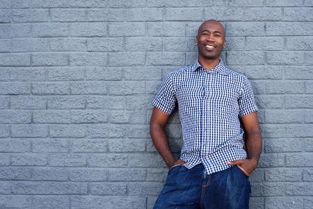 hombres negros: Retrato de hombre afroamericano hermoso que se coloca contra una pared gris