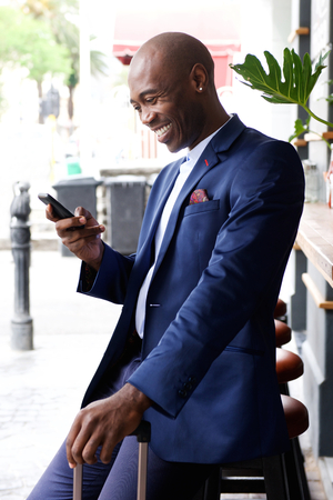 businessman phone: Smiling young african businessman with travel bag reading text message on mobile phone Stock Photo