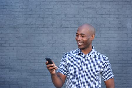 Schließen Porträt der lächelnden afrikanischen Mannes nach oben Blick auf Handy
