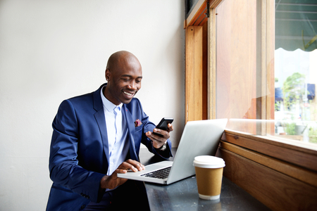 hombre de negocios: Retrato de hombre de negocios africano feliz que usa el teléfono mientras se trabaja en la computadora portátil en un restaurante Foto de archivo