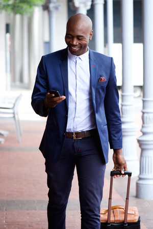 handsome business man: Walking african business man traveling with bag and cell phone Stock Photo