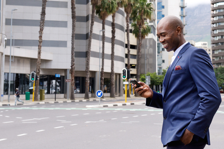 persone nere: Ritratto di un messaggio di testo giovane lettura uomo d'affari sorridente sul suo telefono cellulare mentre si cammina in citt�