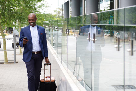 businessman phone: Portrait of an african businessman walking with bag and looking at mobile phone Stock Photo