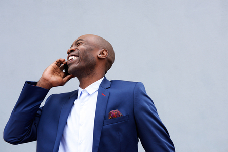 african business man: Close up portrait of smiling businessman talking on mobile phone