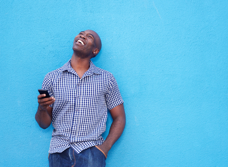 Portrait of smiling african man with a mobile phone standing against blue background