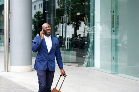 Portrait of an african businessman walking with suitcase and talking on mobile phone