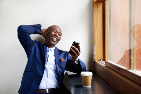 Portrait of smiling businessman sitting at a cafe looking at mobile phone Stock Photo