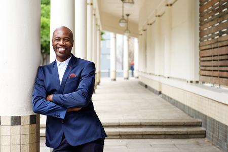 Portret van vertrouwen Afrikaanse zakenman die zich in openlucht met zijn armen gekruist Stockfoto