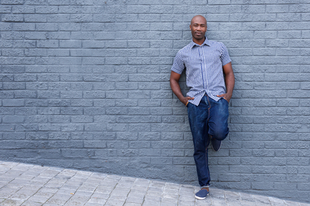 leaning: Full length portrait of a relaxed african american man leaning against wall