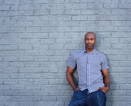 african america: Portrait of african america man standing against a gray wall