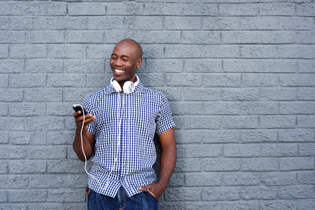 black male: Portrait of happy african young man with headphones and mobile phone