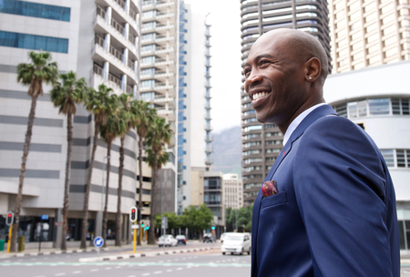 side light: Portrait of a smiling businessman standing in the city