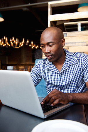 black guy: Portrait of a black guy sitting at cafe table working on laptop