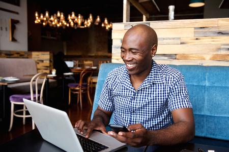 Portret van glimlachende man met een mobiele telefoon zit op cafe met behulp van laptop