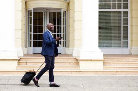 Full length portrait of african businessman walking with bag and mobile phone