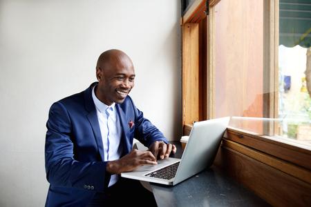 Portret van gelukkige Afrikaanse zakenman zitten in een cafe en werken op de laptop